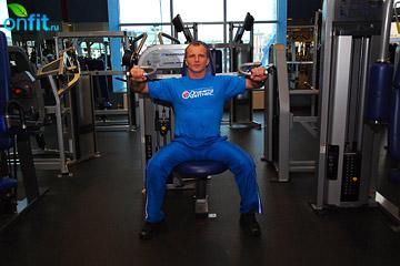 Упражнения на плечи: подъемы рук в стороны на тренажере
